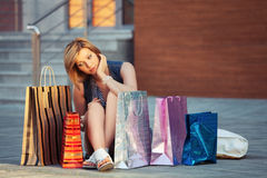 Sad young fashion woman with shopping bags sitting on sidewalk Stock Photos