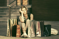 Sad young fashion woman with shopping bags sitting on the sidewalk Royalty Free Stock Images