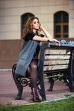 Sad young fashion woman sitting on bench Royalty Free Stock Image