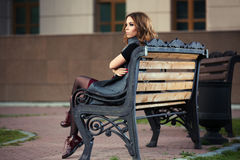 Sad young fashion woman sitting on bench Stock Images