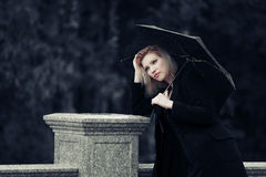 Sad young fashion woman with umbrella in the rain Royalty Free Stock Photography