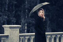 Sad young fashion woman with umbrella in the rain Royalty Free Stock Photos