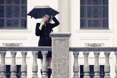 Sad young fashion woman with umbrella walking in city street Stock Photos