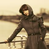 Sad young fashion woman in classic coat and headscarf walking outdoor Royalty Free Stock Photo