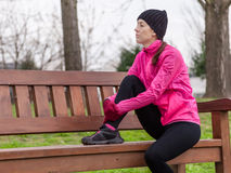 Sad young female athlete sitting on a bench Royalty Free Stock Photography