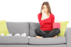 Sad young female sitting on a couch and wiping her eyes from cry. Ing isolated on white background royalty free stock photo