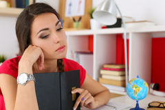 Sad young female student in red dress covering head with book an Stock Photo