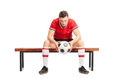 Sad young football player sitting on a bench. Sad young football player sitting on a wooden bench and looking down isolated on white background Royalty Free Stock Photo