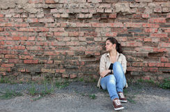Sad young girl. Sitting against a brick wall Stock Image
