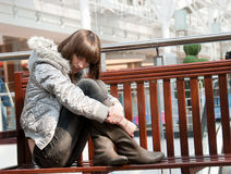 Sad young girl. Sits on a bench in a mall Stock Photos