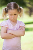 Sad young girl with arms crossed at park Stock Photo