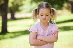 Sad young girl with arms crossed at park Stock Photos