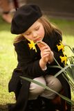 Sad young girl in beret stroking daffodil Stock Photography