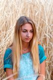 Sad young girl is in the field wheat, in ripe ears Royalty Free Stock Image