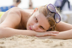 Sad young girl lying on sandy beach and looking to side Royalty Free Stock Photos