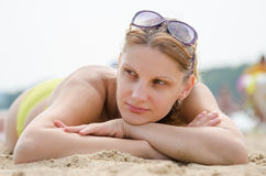 Sad young girl lying on sandy beach and looking to the side Stock Photography