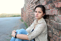 Sad young girl near an brick wall Royalty Free Stock Photo