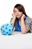 Sad young girl with piggy bank. Sad young girl looking at blue spotted piggy bank. Isolated on white background Royalty Free Stock Photography