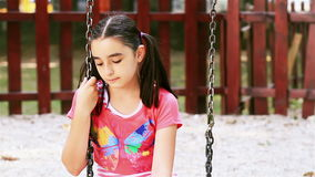 Sad young girl sits on swing stock video