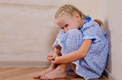 Sad young girl sitting in corner Royalty Free Stock Images