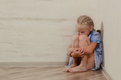 Sad young girl sitting in corner Royalty Free Stock Photos