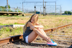Sad young girl sitting lonely on rail track Royalty Free Stock Photos
