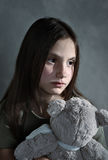 Sad young girl with toy. In grey background Stock Images