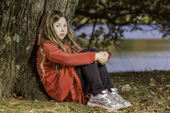 Sad young girl by tree. Young girl, in red outfit leaning against a tree. A look of sadness or thought on her face, vlose up full body shot with lake in the Royalty Free Stock Photo