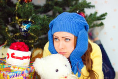 Sad young girl  is under the Christmas tree Royalty Free Stock Images