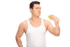 Sad young guy holding a small sandwich Royalty Free Stock Image