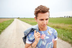 Sad young hippie man walking along country road Stock Image