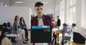 Sad young male handsome European manager is fired and quitting job at multiethnic office, walking away with stuff box. Upset colleagues watch dismissed worker stock video