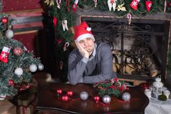Sad young male seated with christmas tree royalty free stock photo