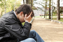 Sad young man. Sitting in the autumn park Stock Photos
