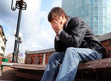 Sad young man. Sorrowful young man sitting on the city street Stock Image