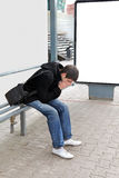 Sad Young Man. Sitting at the Bus Stop at the City Street Stock Photography