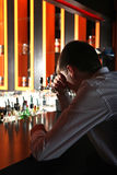 Sad Young Man at the Bar. Sad and Lonely Young Man Sitting in the Darkness at the Bar counter Stock Photo