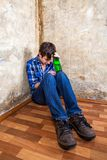 Sad Young Man. With a Beer by the Old Wall royalty free stock image