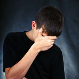 Sad Young Man. On the Black Background hide the Face Stock Photos