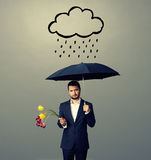 Sad young man with black umbrella. And drooped flowers standing under drawing storm cloud. photo over grey background Royalty Free Stock Photography