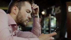 Sad young man with cell phone in a bar. Close up of sad young man looking at the cell phone sitting at the table in a restaurant stock video