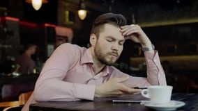 Sad young man with cell phone in a bar. Sad young man is looking at the cell phone sitting at the table with coffee in a restaurant stock footage