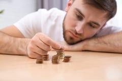 Sad young man counting money at home. Closeup stock photos