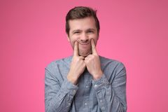 Sad young man dressed in blue shirt makes faces trying to stay optimistic royalty free stock images