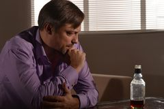 Sad young man drinks whiskey Stock Photography