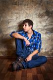 Sad Young Man. On the Floor by the Old Wall Stock Image