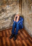 Sad Young Man. On the Floor by the Old Wall Royalty Free Stock Photography