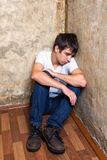 Sad Young Man. On the Floor by the Old Wall Stock Images