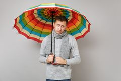 Sad young man in gray sweater, scarf holding colorful umbrella on grey background studio portrait. Healthy