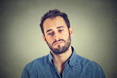 Sad young man on gray wall background stock image